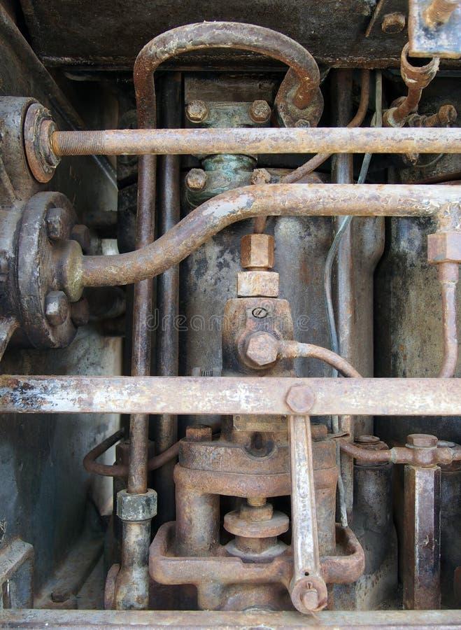 关闭显示生锈的管子的大老被放弃的海洋柴油引擎和圆筒和螺栓 免版税库存图片