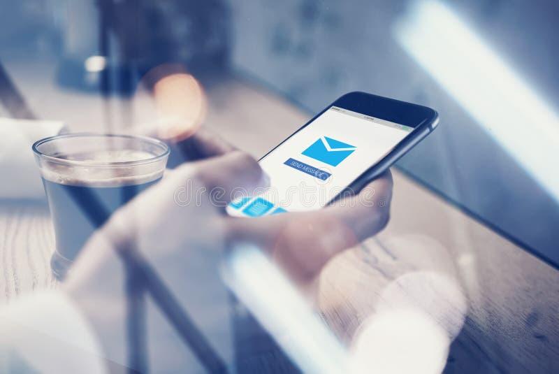 关闭普通举行在短信的消息的女性手上的设计巧妙的电话 送在屏幕上的消息象 杯 图库摄影