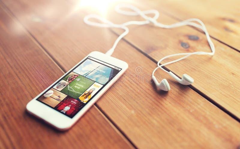 关闭智能手机和耳机在木头 库存照片