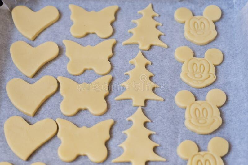 关闭曲奇饼面团用不同的形状在烘烤shee说谎 库存图片