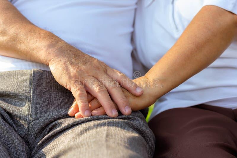 关闭更旧的夫妇手 更旧的丈夫用途手为鼓励他心爱的妻子结合在一起使更旧的wife's手 库存照片