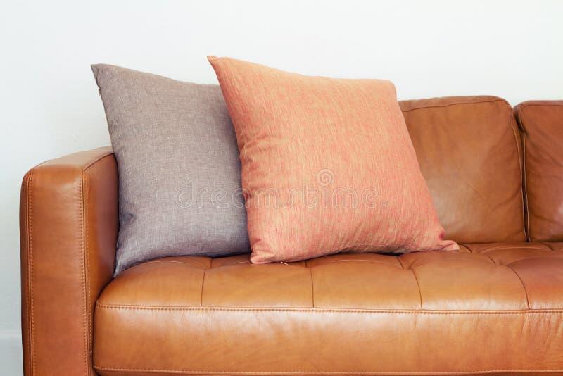 关闭有亚麻制坐垫的棕褐色的皮革沙发 免版税库存照片