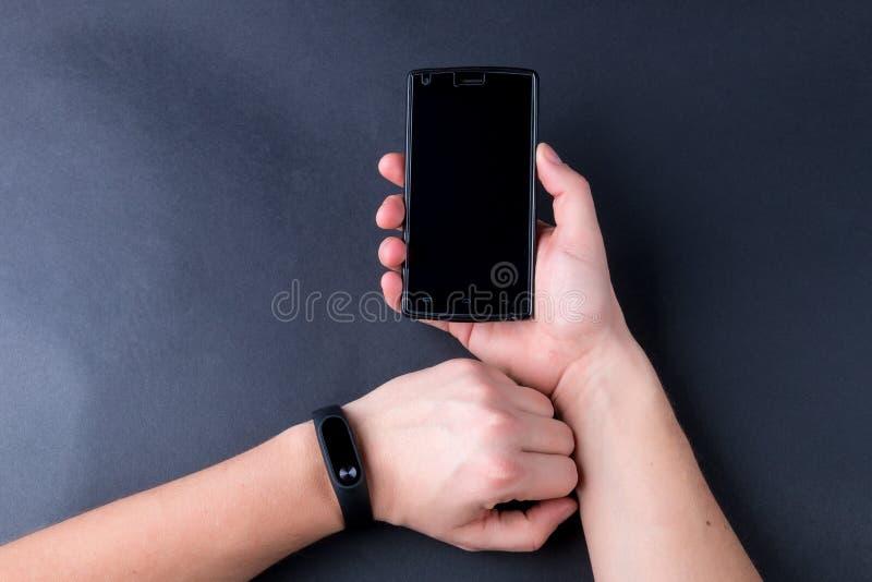 关闭有健身跟踪仪和智能手机的人的手在黑背景 免版税库存图片