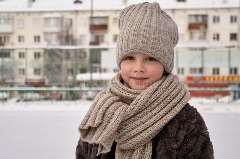 关闭有冬天被编织的帽子的微笑的逗人喜爱的女孩 室外射击有未聚焦的被弄脏的背景 免版税库存照片