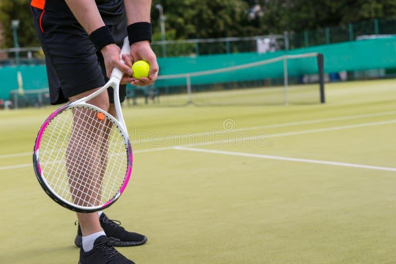 关闭有准备的网球的男性球员` s手服务 免版税库存图片