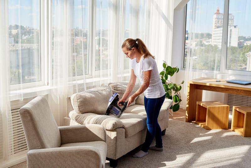 关闭有吸尘器的,拷贝空间妇女手 有吸尘器的妇女清洗的沙发 家庭和春天cleanig 免版税库存照片