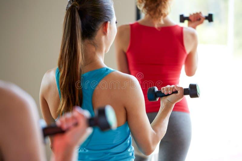 关闭有哑铃的妇女在健身房 免版税库存图片