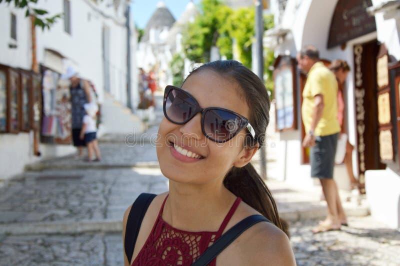 关闭有太阳镜的时髦的少妇微笑在意大利风景背景中的  有白色的秀丽妇女完善微笑looki 库存照片