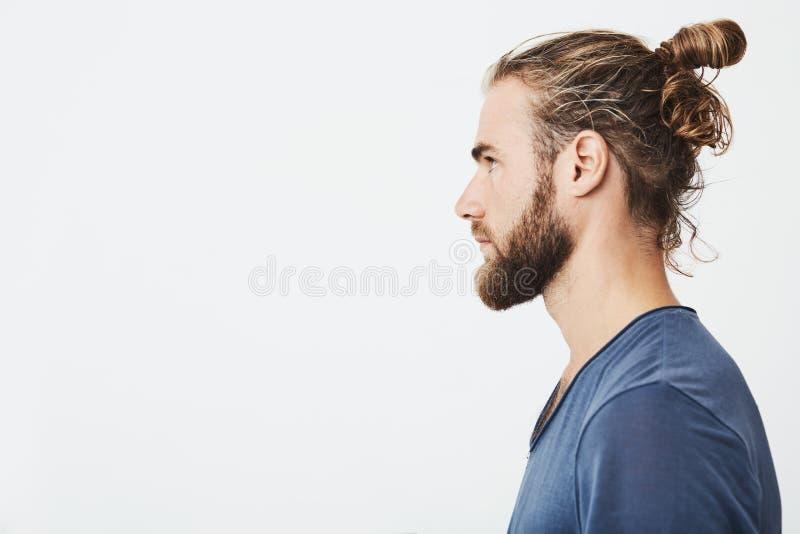 关闭有头发的悦目有胡子的行家人在小圆面包,在站立在外形的蓝色T恤杉,看在旁边 免版税库存照片