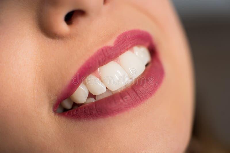 关闭有完善的牙的美丽的年轻微笑的妇女在牙齿办公室 免版税库存图片