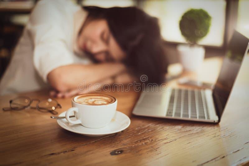 关闭有很多在咖啡杯的咖啡有女商人的疲乏从工作和手提电脑背景 放松睡觉 图库摄影