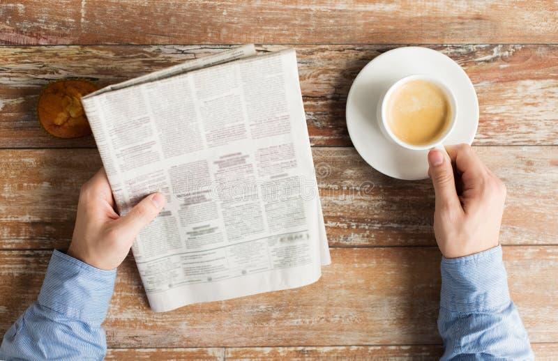 关闭有报纸和咖啡的男性手 免版税图库摄影