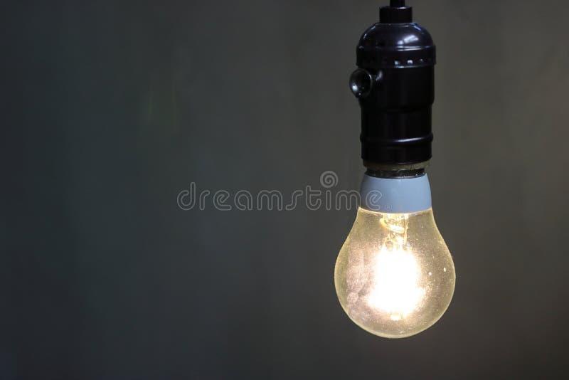 关闭有拷贝空间的,电灯泡一盏减速火箭的轻的灯装饰在黑背景中 图库摄影