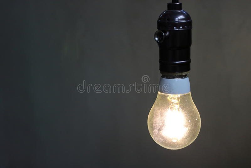 关闭有拷贝空间的,电灯泡一盏减速火箭的轻的灯装饰在黑背景中 免版税库存图片