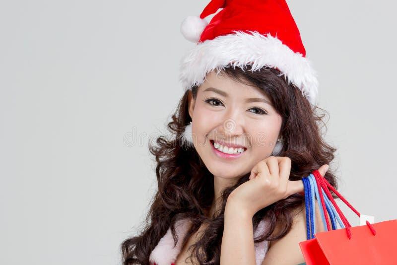 关闭有拿着五颜六色的购物袋的圣诞老人礼服的亚裔妇女 库存图片