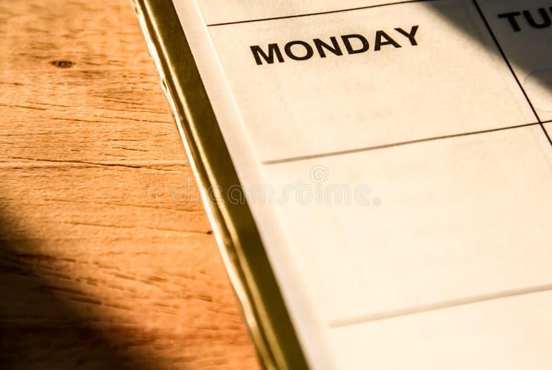 关闭有星期一词的笔记本在木桌上 免版税图库摄影