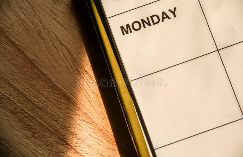 关闭有星期一词的笔记本在木桌上 库存照片
