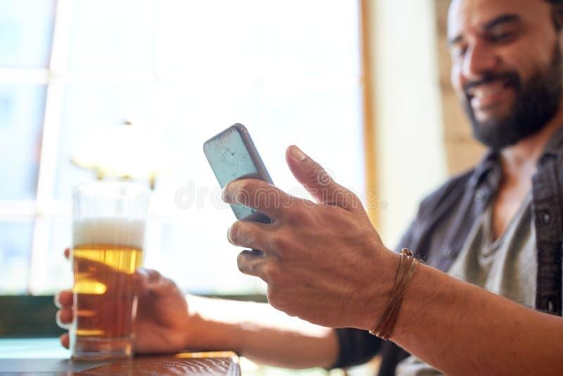 关闭有智能手机和啤酒的人在客栈 免版税库存图片