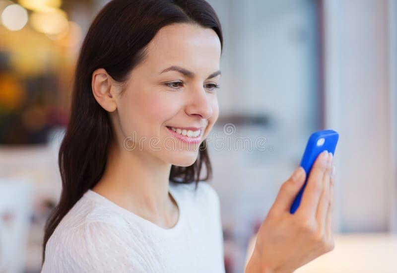关闭有智能手机的微笑的妇女在咖啡馆 库存照片