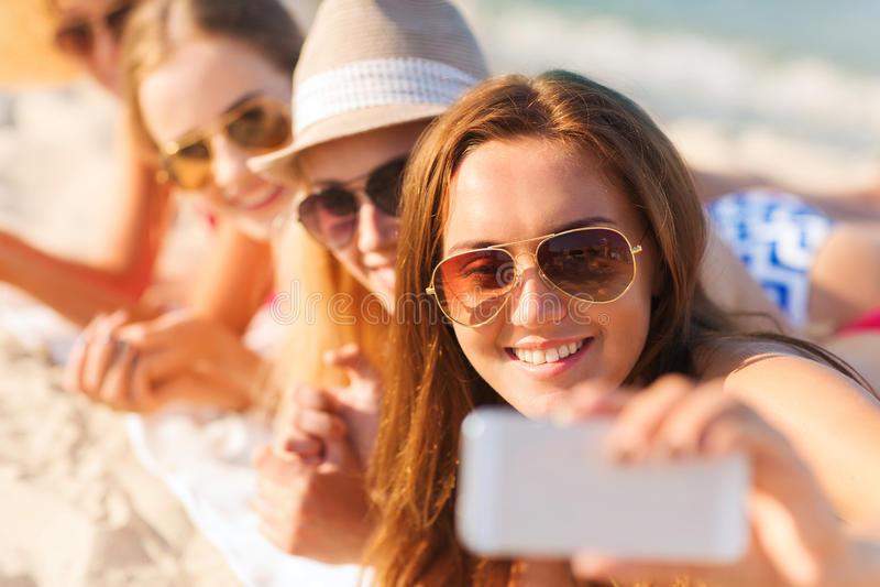 关闭有智能手机的微笑的妇女在海滩 免版税库存图片