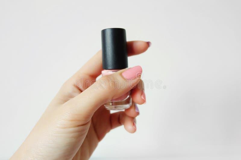 关闭有桃红色被绘的钉子的手 与桃红色瓶的美好的桃红色钉子修指甲在妇女是在白色背景的手 库存照片