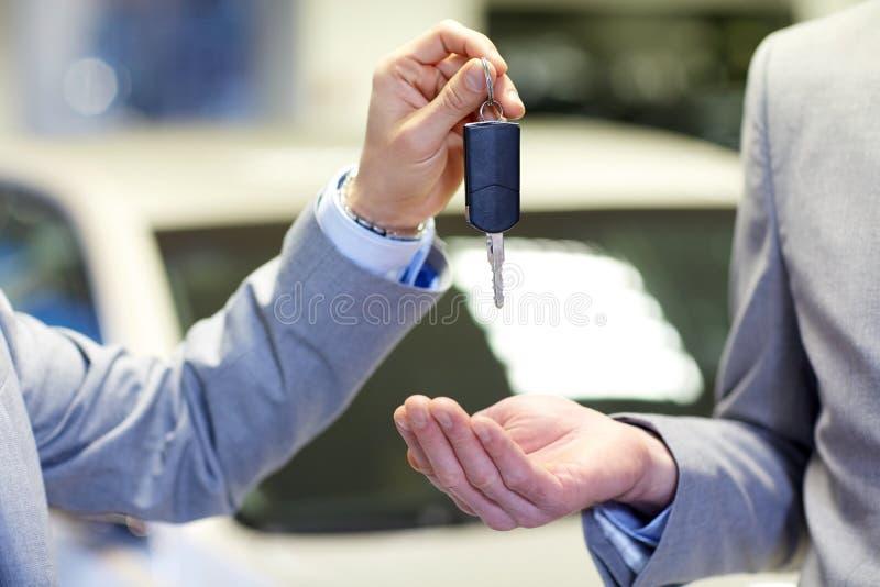 关闭有汽车钥匙的男性手在自动沙龙 库存图片