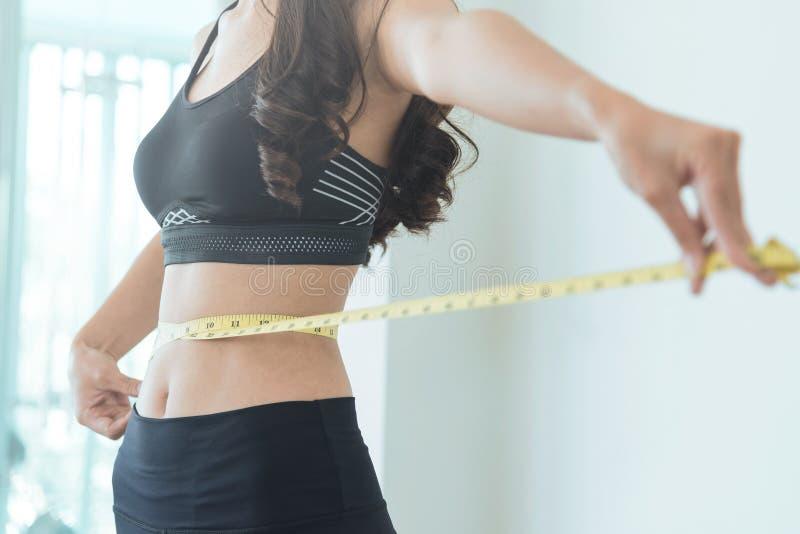 关闭有测量的磁带的亭亭玉立的亚洲妇女腰部 复制温泉 免版税图库摄影