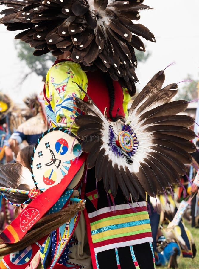 关闭有用羽毛装饰的熙来攘往和头饰的一位美国本地人花梢舞蹈家 免版税图库摄影