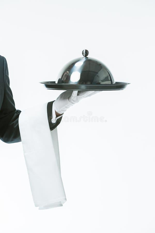 关闭有盘子和金属钓钟形女帽盒盖盖子的侍者手 免版税库存图片