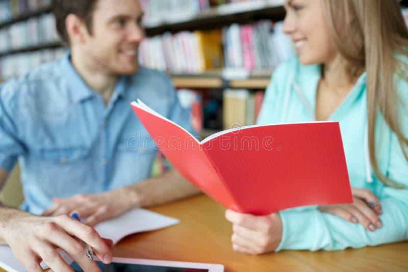 关闭有笔记本的学生在图书馆里 免版税库存照片