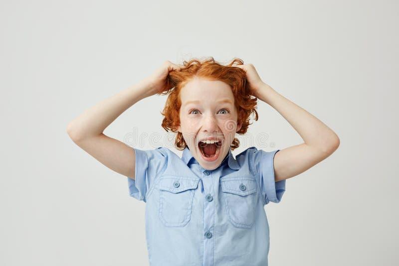 关闭有红色拉扯头发用手的头发和雀斑的滑稽的小男孩,尖叫与惊奇的表示 库存图片