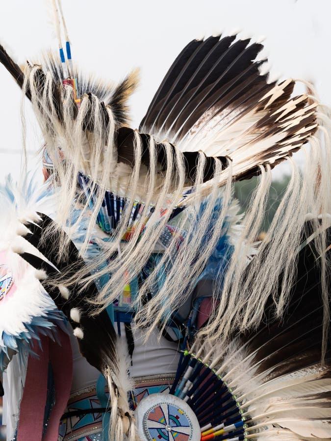 关闭有老鹰羽毛头饰的花梢与毛皮飘带的舞蹈家和熙来攘往 免版税库存照片