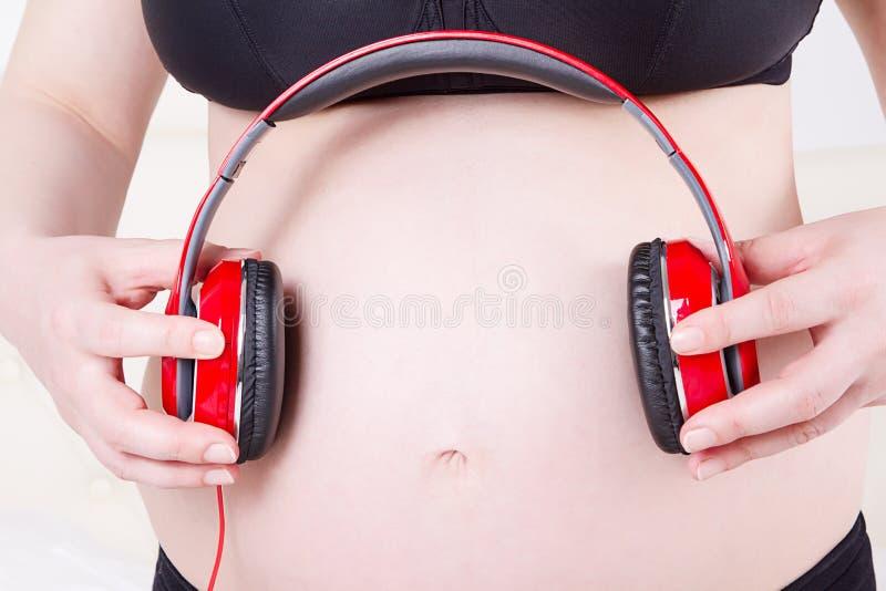 关闭有耳机的孕妇在腹部listenin 免版税库存照片