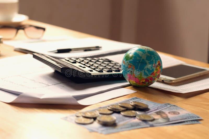 关闭有计算器和金钱的地球玩具在书桌办公室, acc 图库摄影