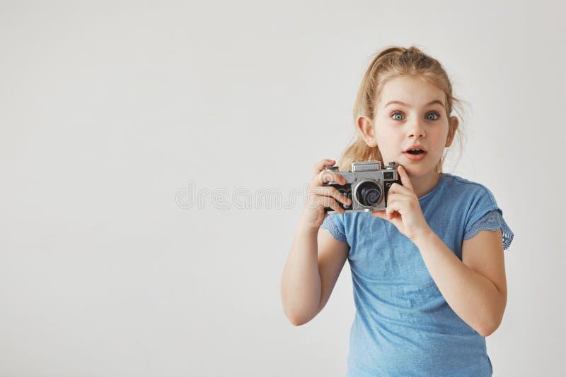 关闭有轻的头发的小逗人喜爱的女孩在看在与惊奇的面孔表示的照相机的蓝色T恤杉,举行 免版税库存图片