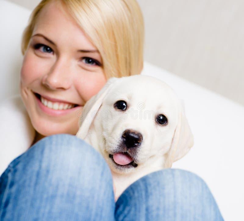 关闭有逗人喜爱的小狗的妇女在她的膝盖 免版税库存照片