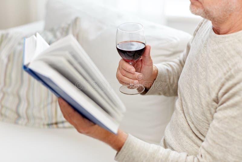 关闭有酒阅读书的老人 库存照片