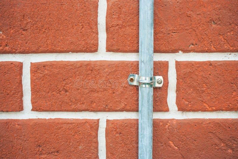 关闭有铁在红色葡萄酒砖墙上设定的管子锁的钢水管 库存照片