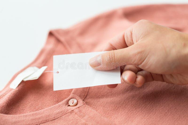 关闭有价牌和衣物项目的手 免版税库存图片