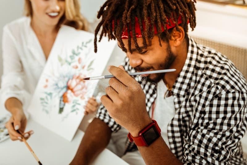 关闭有dreadlocks的年轻时髦的深色头发的艺术系学生 免版税库存图片