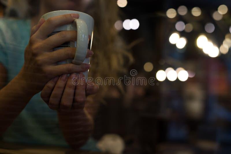 关闭杯子 妇女在咖啡享用 免版税库存图片