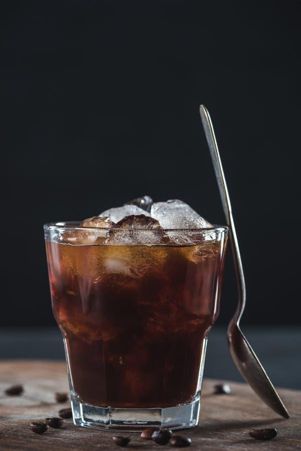 关闭杯看法寒冷与匙子的煮的咖啡在木切板 免版税库存图片