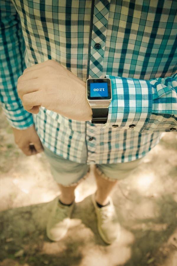 关闭检查在巧妙的手表app的男性手时间 库存图片
