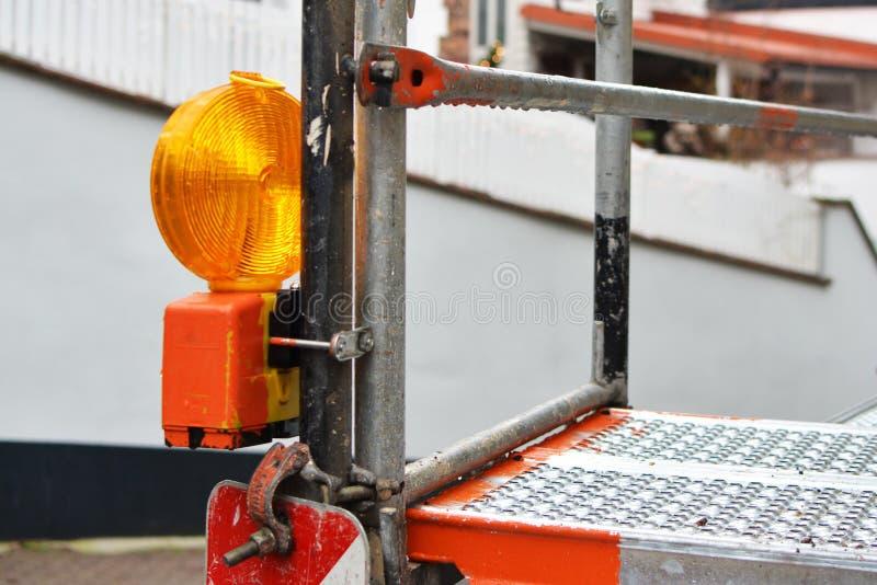 关闭橙色反射器警告灯附有绞刑台在工地工作 免版税库存图片