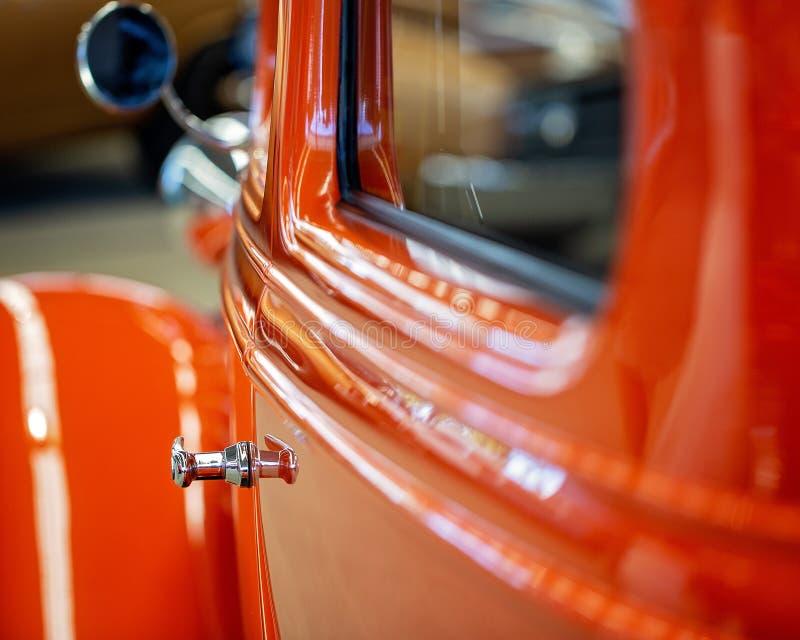 关闭橙色葡萄酒旧车改装的高速马力汽车汽车的门 库存照片