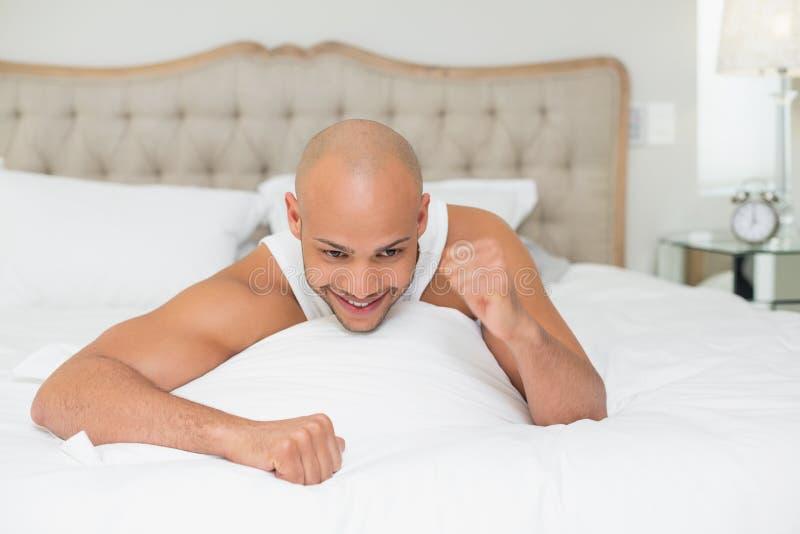 关闭欢呼在床上的一个人 库存照片