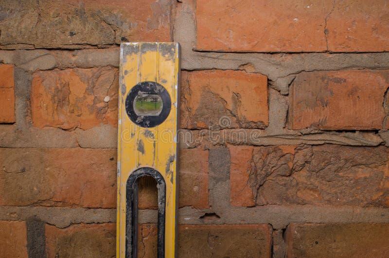 关闭水平仪显示水平与浅景深对砖墙 库存照片