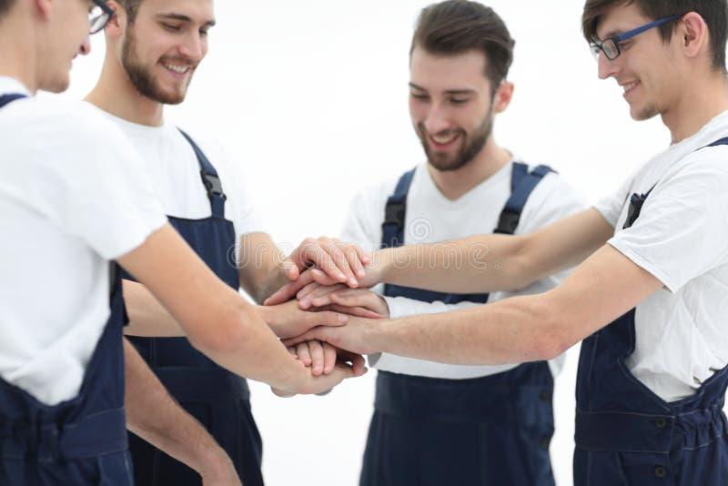 关闭汇集他们的手的年轻搬家工人顶视图  免版税库存图片