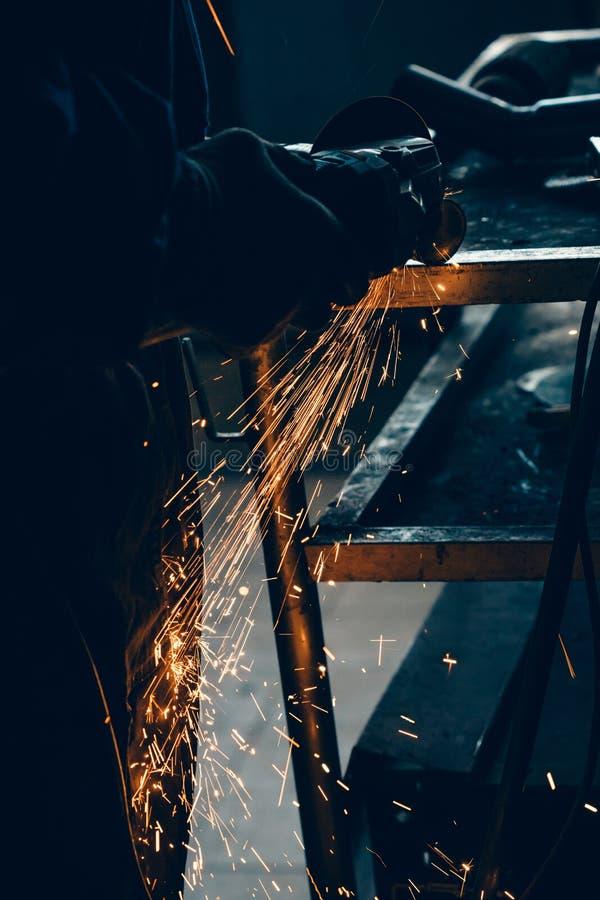 关闭汽车修理师手焊接磨床 磨床火花,当切开汽车排气管时 免版税图库摄影