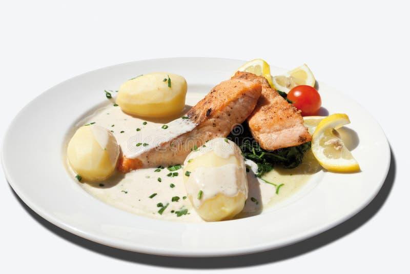 关闭油煎的三文鱼用菠菜,煮的土豆 免版税库存照片